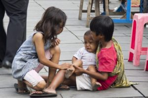Children crouched/sitting on street - empathetic - one holding an infant who's crying, the other sympathetic to their plight.