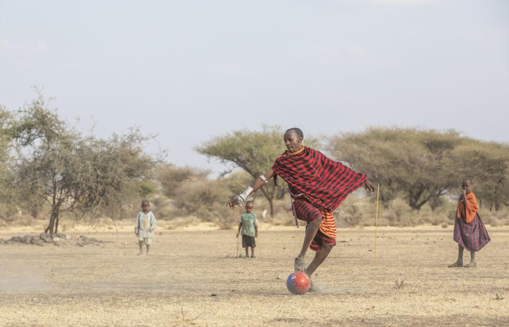 maasai warriors playing football in savannah