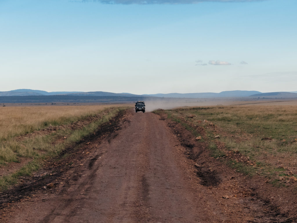 A Jeep SUV on a dusty dirt road steadily driving forward, with surrounding savannah landscape with a hilly range backdrop on a sunny day