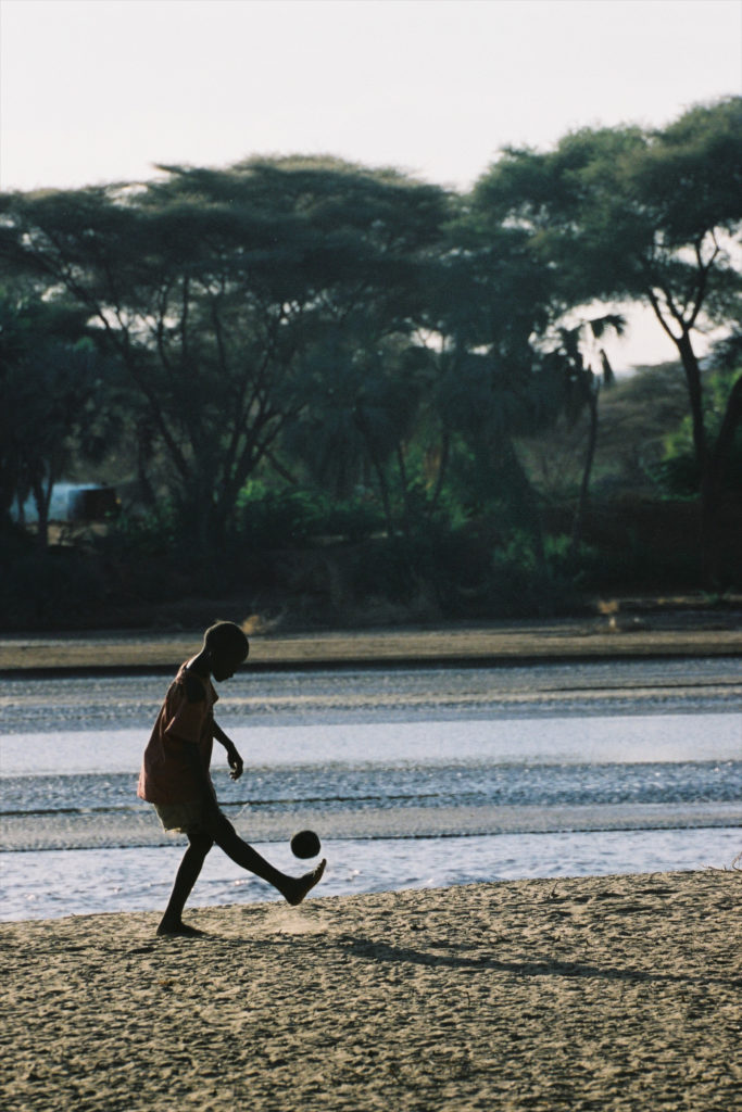 A local happy boy playing soccer balancing the ball in the air and kicking at a dry riverbed.