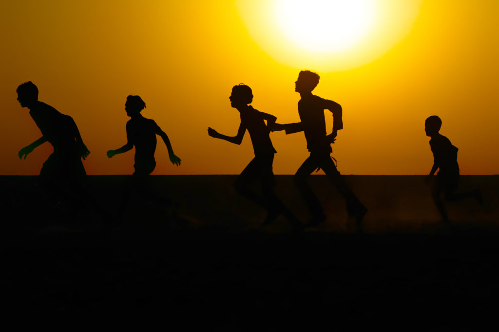 Silhouette of boys playing in a field against a warm sunrise sky