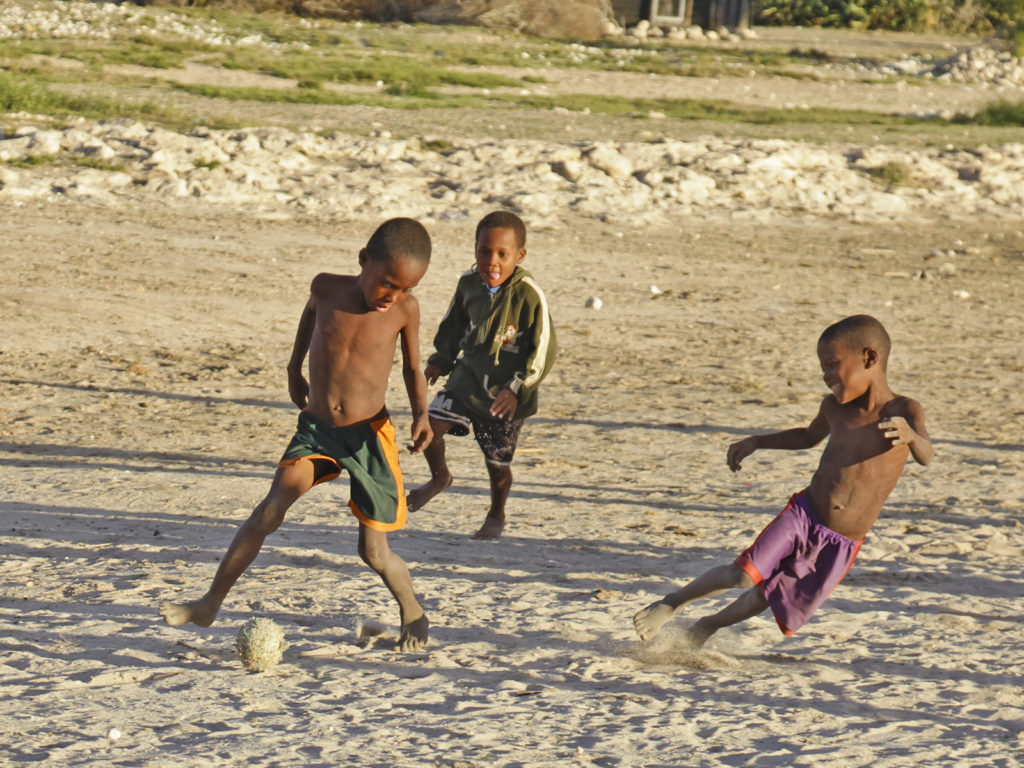 Three young Vezo boys playing on the beach with a football made out of recycled materials,